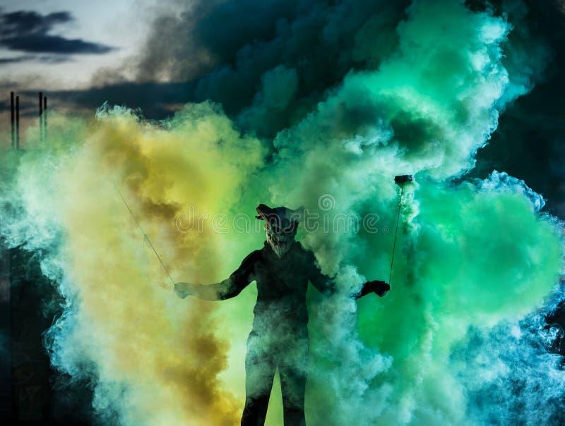 有色的烟围拢的可怕面具的恶魔 库存照片