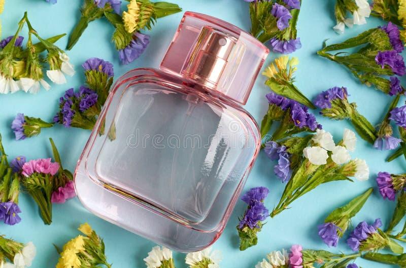 有色的花的香水瓶在蓝色背景构成 免版税库存图片