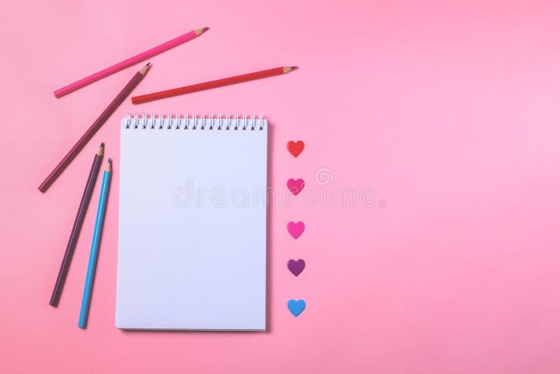有色的铅笔和桃红色背景的白色笔记本 免版税库存图片