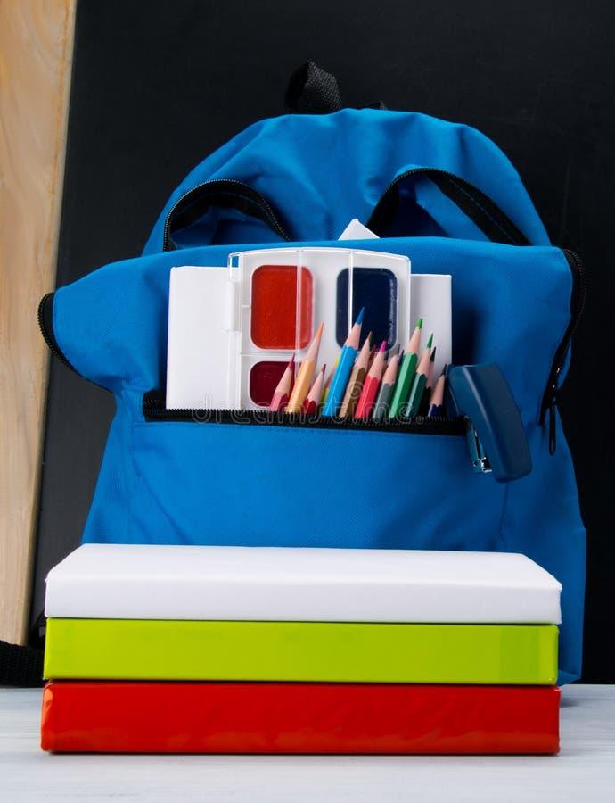 有色的铅笔和油漆的蓝色背包在黑背景和在书旁边 库存照片