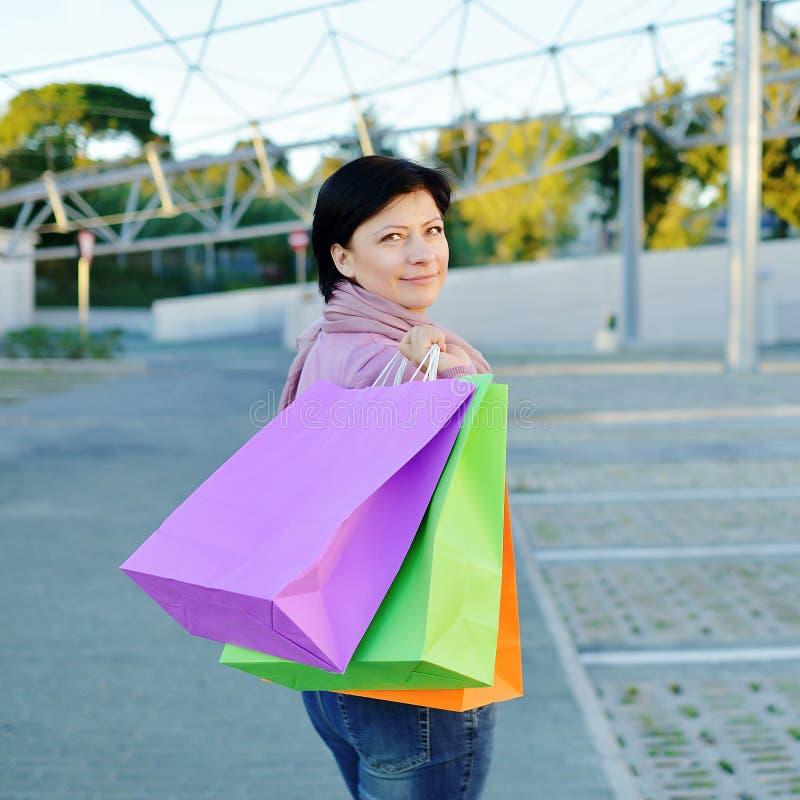 有色纸购物袋的妇女在手上 免版税库存照片