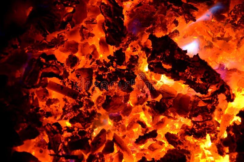 有色金属灼烧的芯片在煤炭的与木头 库存图片