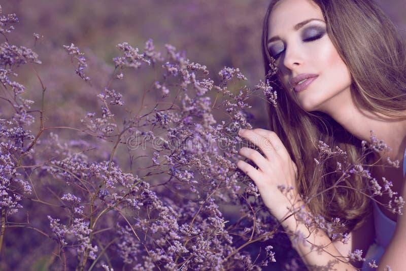 有艺术性的魅力的华美的妇女组成和长的头发软软地接触与闭合的眼睛的紫罗兰色花享受他们的芳香的 库存图片