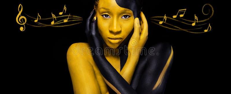 有艺术时尚构成的快乐的年轻非洲妇女 有黑和黄色构成和笔记的令人惊讶的妇女 五颜六色 免版税库存图片