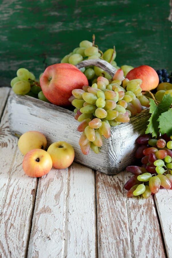 有芬芳成熟苹果和葡萄水果篮的木箱 自然有机果子 免版税库存照片