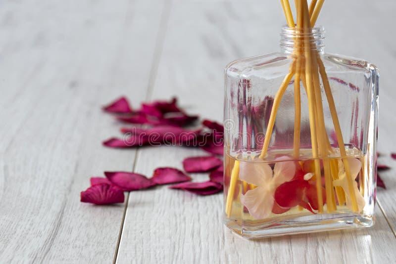 有芬芳的里德分散器在有玫瑰花瓣的一个玻璃瓶子 库存图片