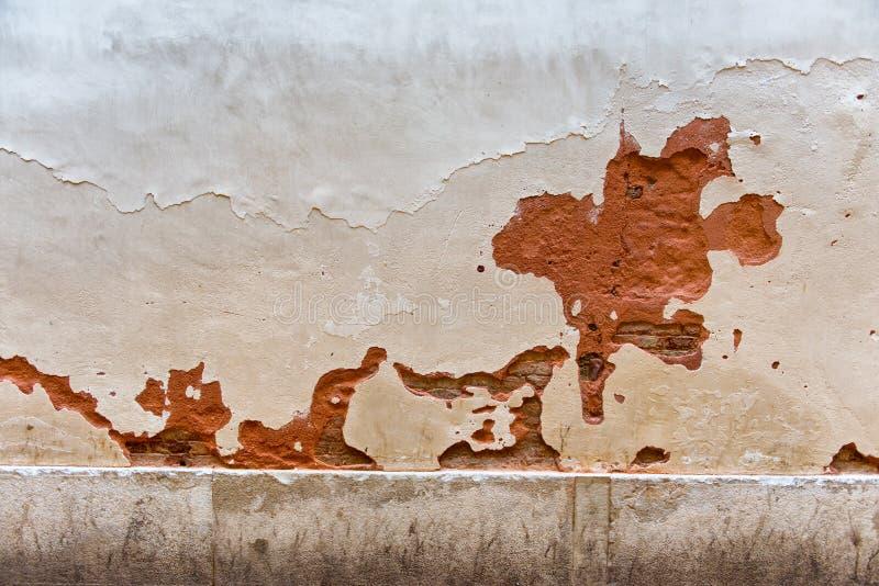 有芯片和镇压的被绘的红色石墙 库存照片