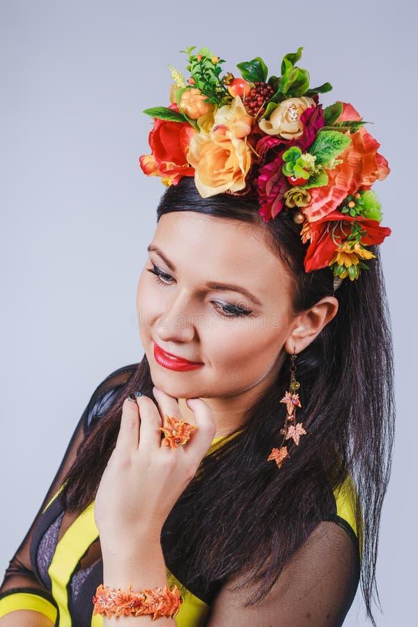 有花冠的可爱的妇女在秋天样式的 库存照片