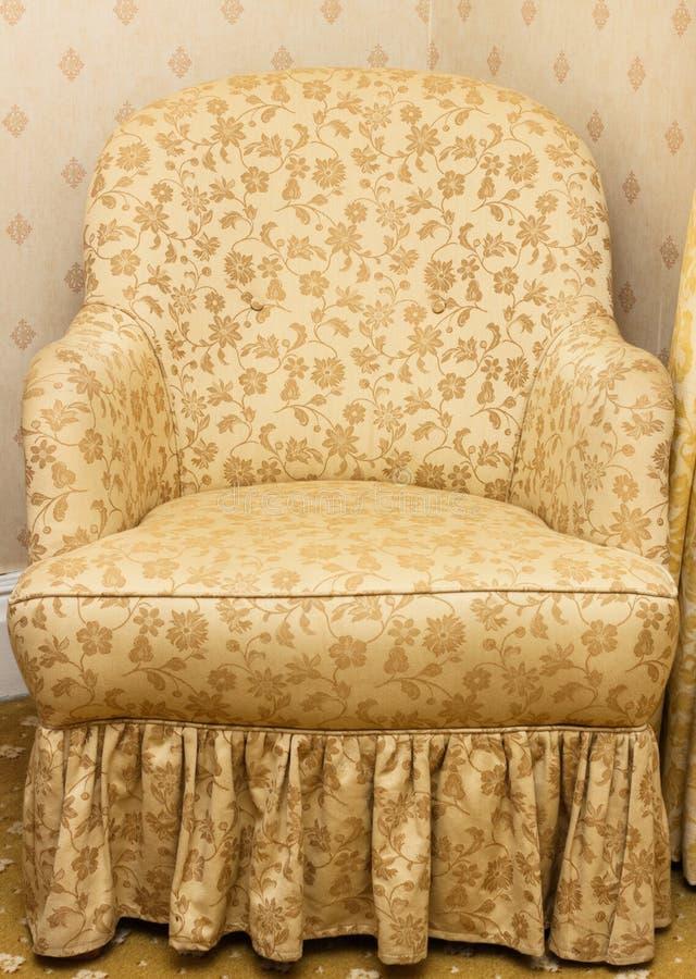 有花卉模式的空的减速火箭的棕色扶手椅子 免版税图库摄影