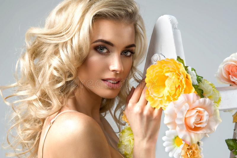 有花卉的精美白肤金发的妇女 库存图片