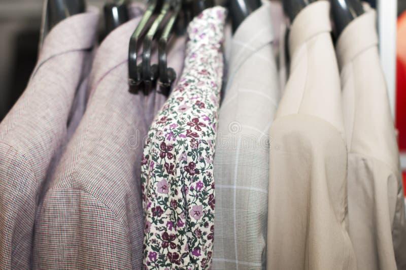 有花印刷品的衬衣和在一个挂衣架的夹克米黄颜色在商店 库存照片