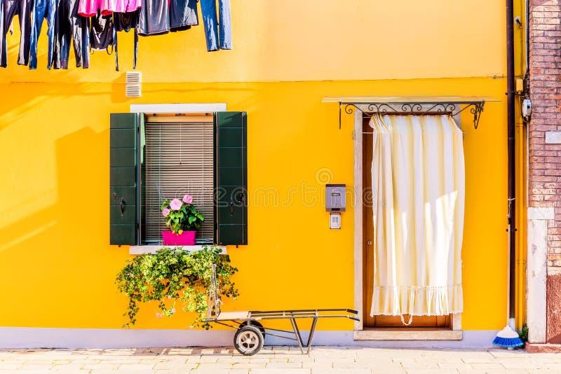 有花和植物的黄色房子 五颜六色的房子在威尼斯,意大利附近的Burano海岛 免版税库存图片