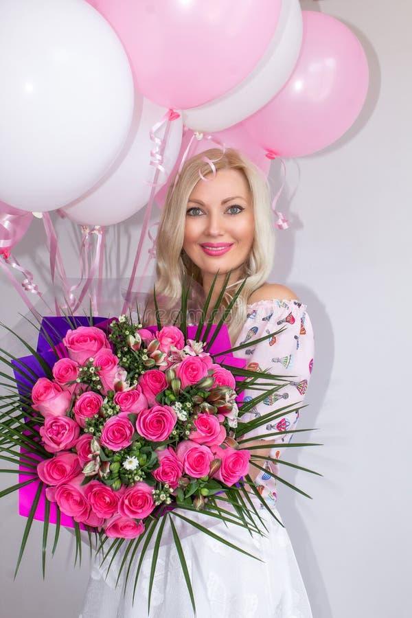 有花和气球花束的美丽的白肤金发的妇女  快乐的情感 庆祝 免版税图库摄影