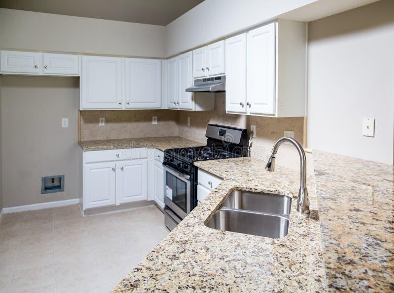 有花岗岩工作台面和不锈钢水槽的新的厨房 库存照片