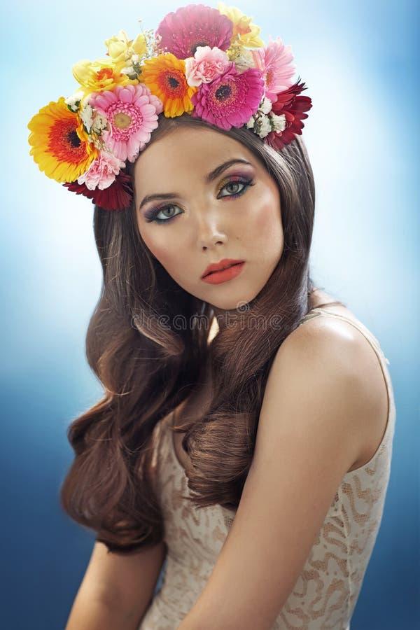 有花帽子的年轻俏丽的女孩 免版税库存图片