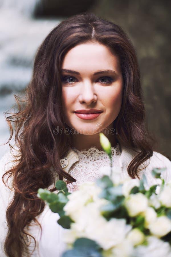有花新娘花束的美丽的俄国女孩  免版税图库摄影