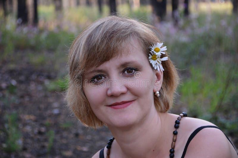 有花春黄菊的美丽的女孩在头发 免版税图库摄影