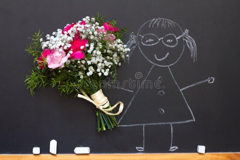 有花束的女孩在黑板老师天摘要概念 免版税库存照片