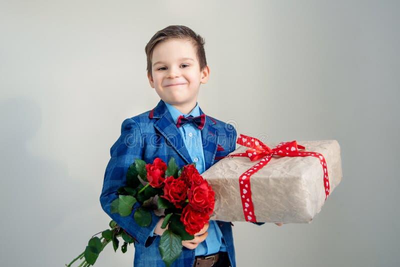 有花束的微笑的男孩和在轻的背景的一件礼物 库存照片