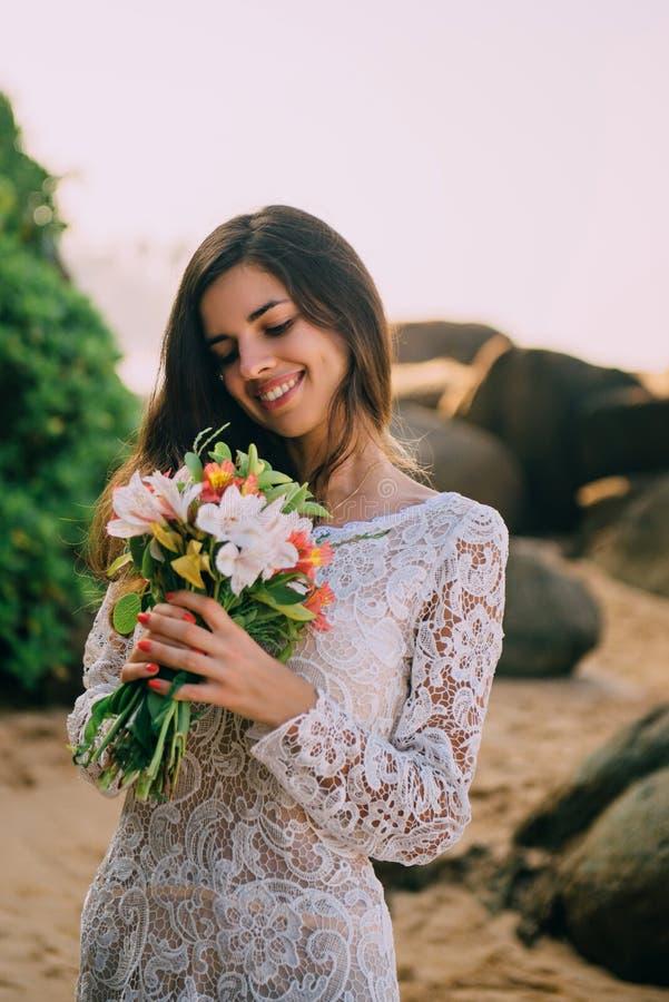 有花束的新娘在手上在海滩和微笑站立 免版税图库摄影