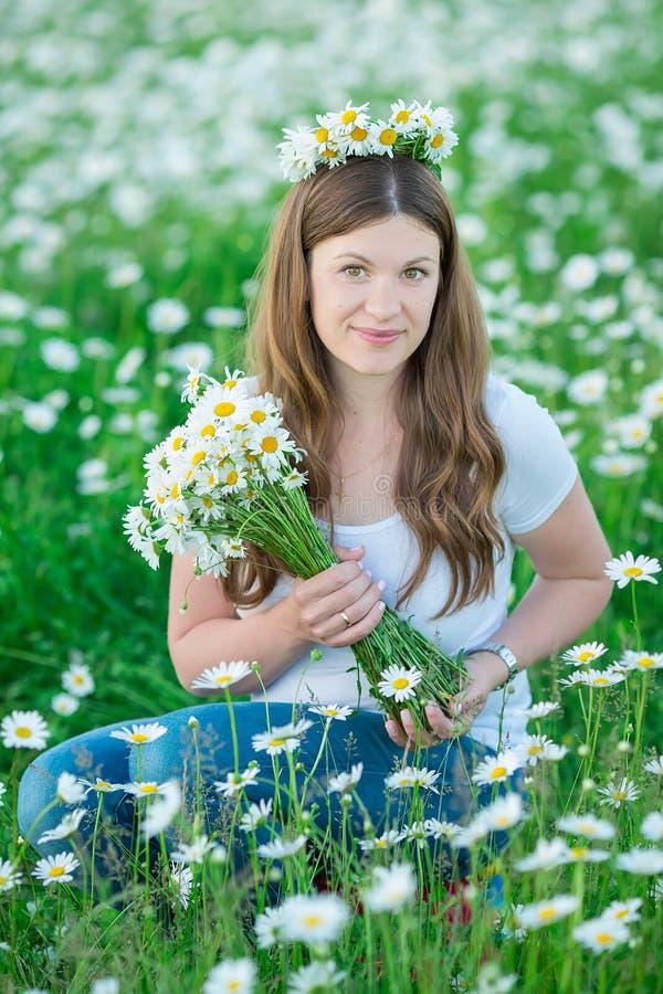 有花束的无忧无虑的可爱的女孩夫人妇女在春黄菊的神仙的领域 夏天自由享受概念 免版税库存照片