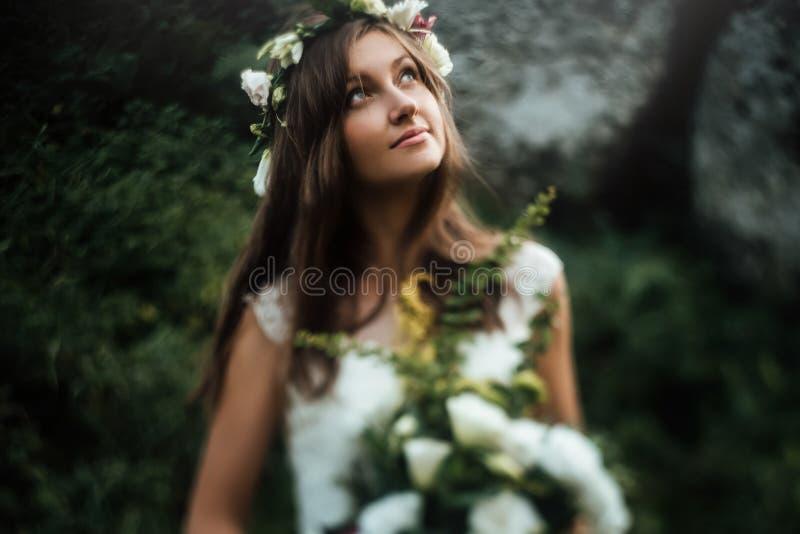 有花束的时髦的肉欲的boho新娘在岩石和森林背景  免版税图库摄影
