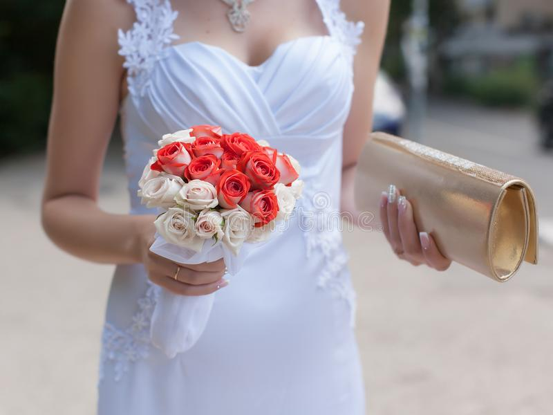 有花束的走在街道上的新娘和手提袋 免版税库存照片
