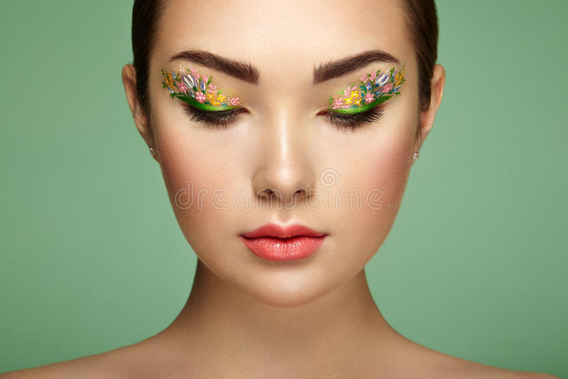 有花构成眼睛的年轻美丽的妇女 免版税库存照片