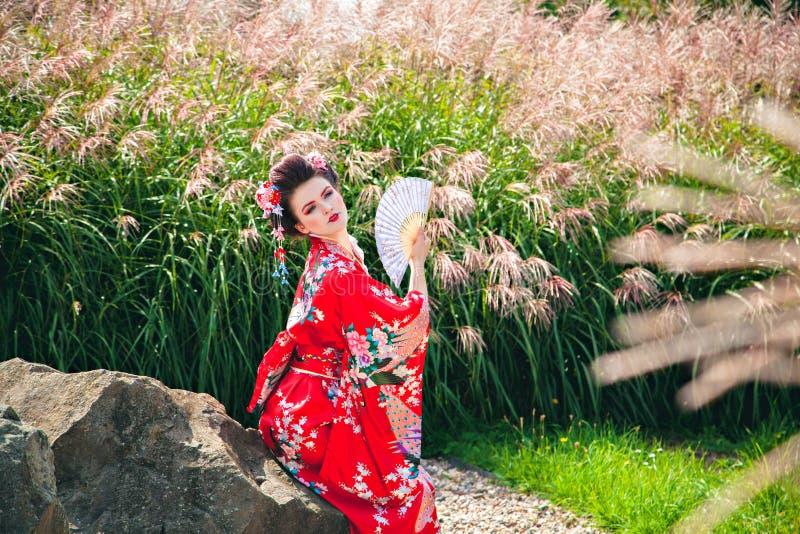 有花梢构成的妇女作为日本艺妓在庭院里 图库摄影