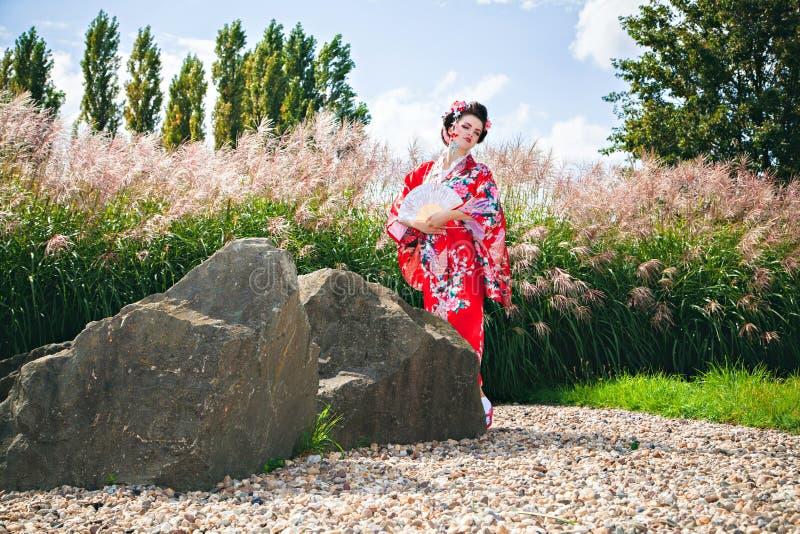 有花梢构成的妇女作为日本艺妓在有爱好者的庭院里 免版税库存图片