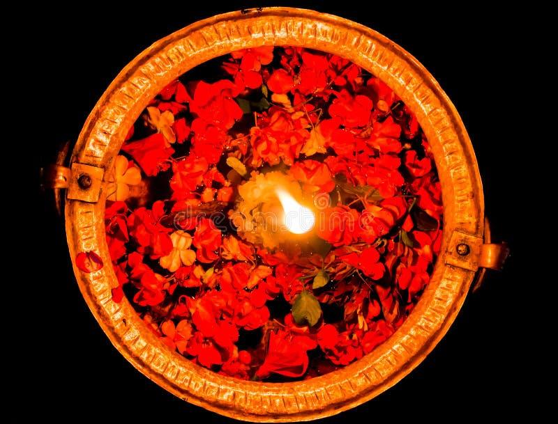 有花瓣和被点燃的蜡烛的水碗 库存图片