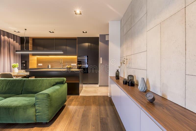 有花瓶和时钟的碗柜在与绿色天鹅绒沙发和黑暗的厨房角落的现代典雅的客厅内部 图库摄影