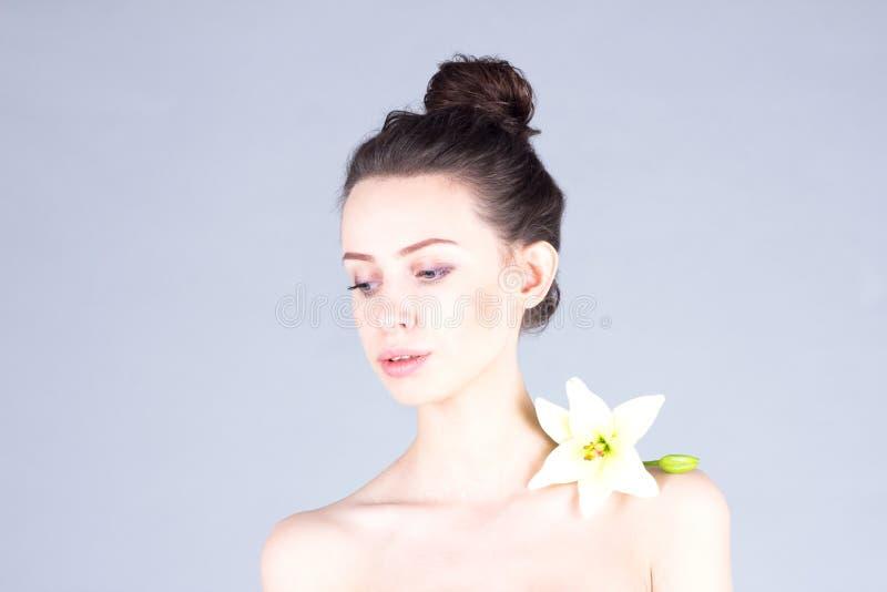 有花的可爱的妇女在看她的肩膀下来 美丽的纵向皮肤 Skincare 库存照片