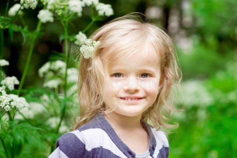有花的可爱的微笑的白肤金发的小女孩在她的头发 免版税库存图片
