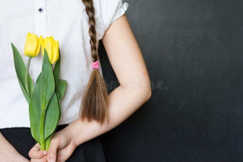 有花的女孩反对黑板庆祝母亲节背景概念 免版税库存照片
