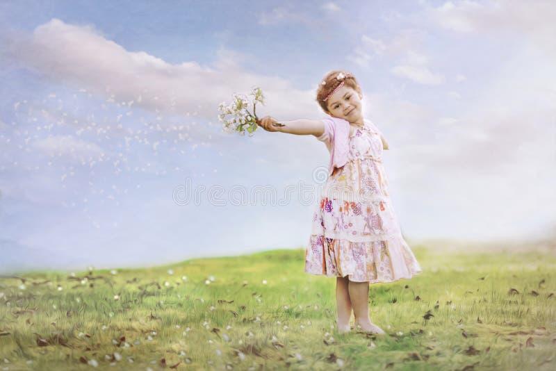有花的女孩在吹的风 免版税库存照片