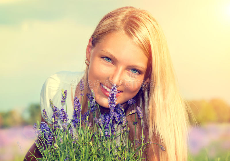 有花的女孩在淡紫色领域 免版税库存图片
