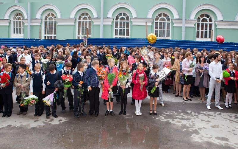 有花的孩子在学校附近在第一天2011年9月1日的学校在圣彼德堡,俄罗斯 免版税库存图片