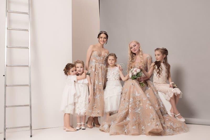 有花的小俏丽的女孩在婚礼礼服穿戴了 免版税库存照片