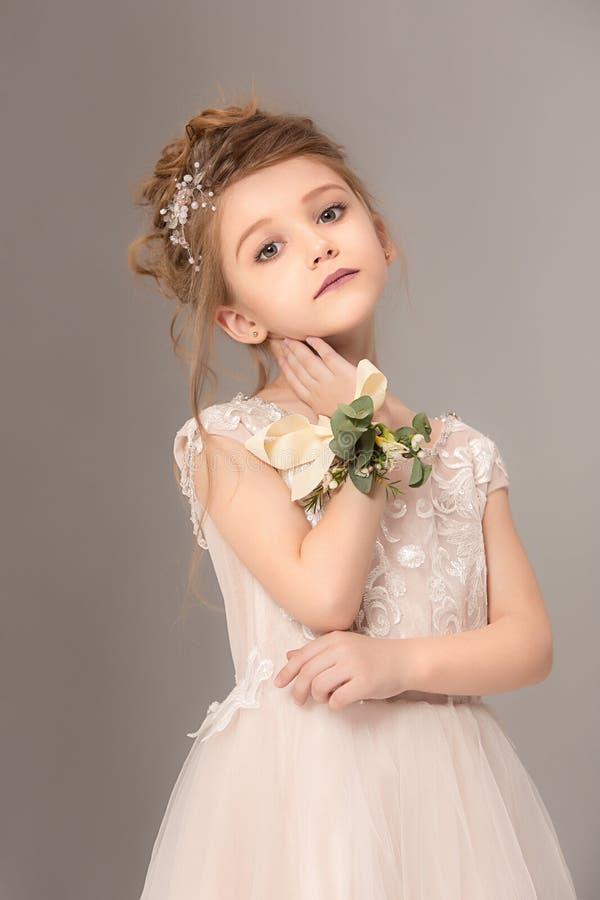 有花的小俏丽的女孩在婚礼礼服穿戴了 免版税库存图片