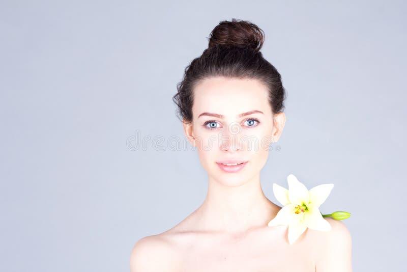 有花的微笑的可爱的妇女在她的肩膀 清洗皮肤妇女 Skincare 图库摄影
