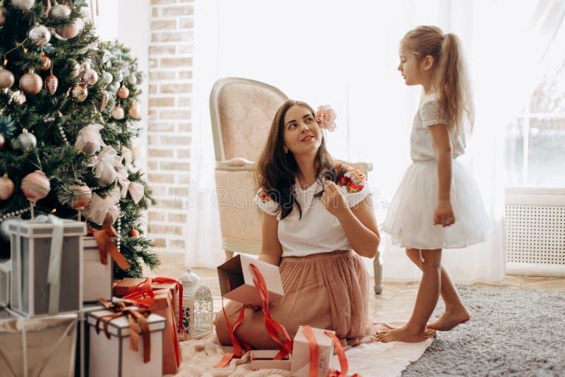 有花的愉快的年轻母亲在她的头发和她的好衣服的小女儿在新年的树附近坐和开放 库存图片