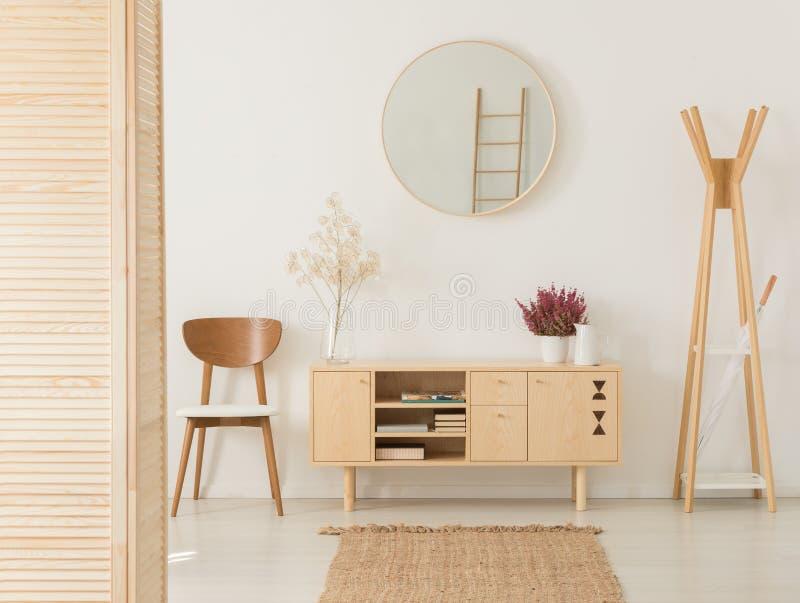 有花的木内阁在时髦的棕色椅子和木挂衣架之间 免版税库存照片