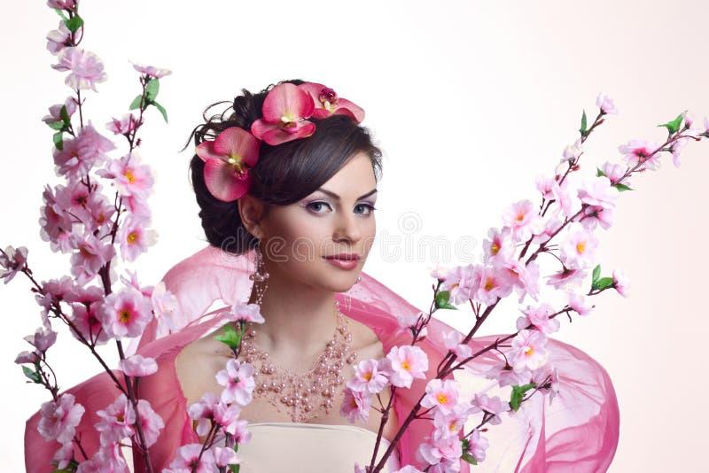 有花的深色的美丽的妇女 免版税库存图片
