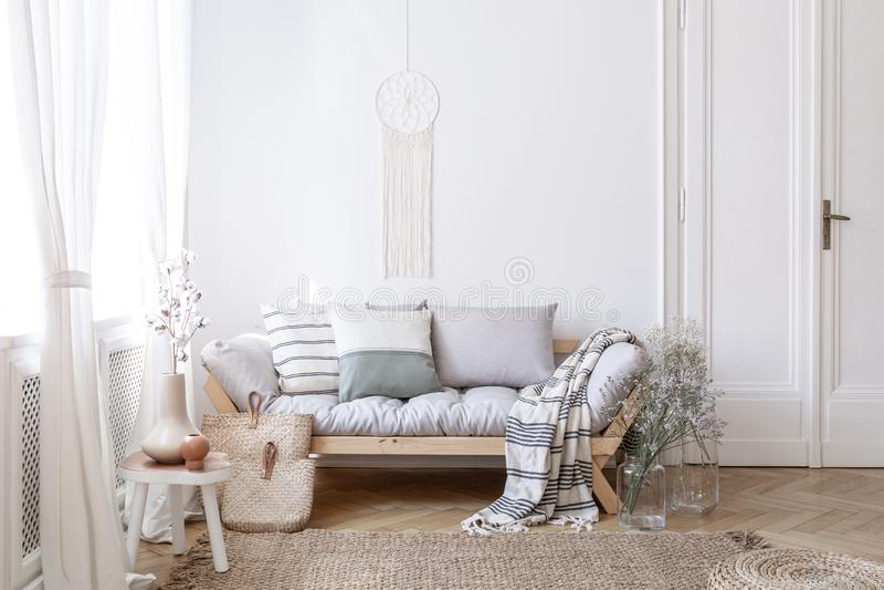 有花的玻璃花瓶在与手工制造dreamcatcher花边的明亮和自然客厅内部在白色墙壁上 库存图片
