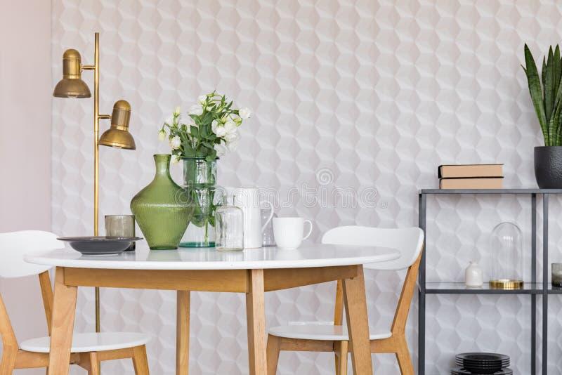 有花的玻璃花瓶在与板材、咖啡杯和瓶子,与拷贝空间的真正的照片的白色木桌上 皇族释放例证