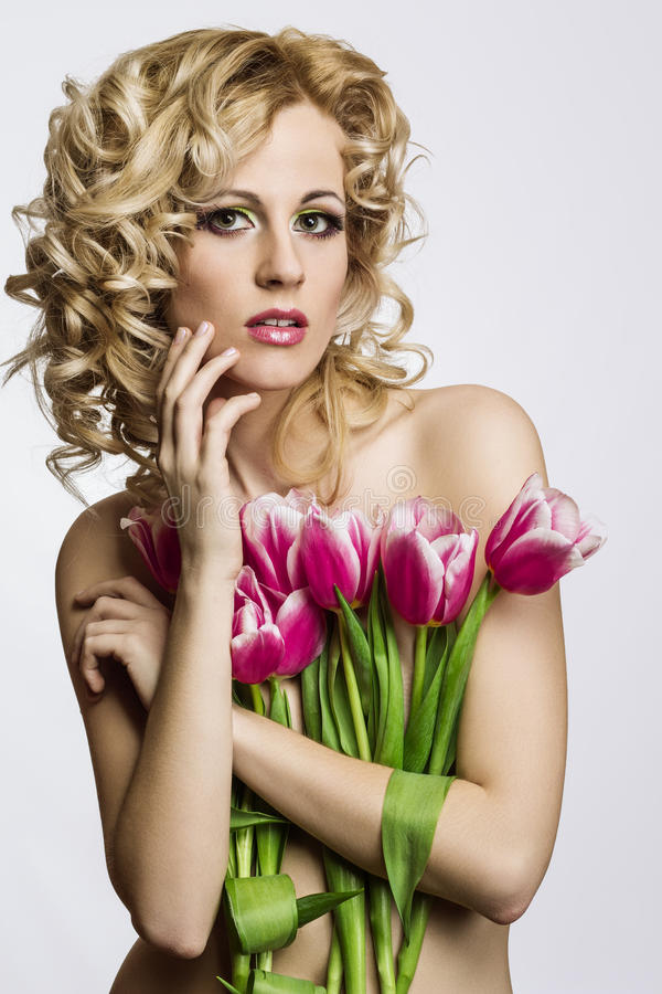 有花的白肤金发的美丽的妇女 库存照片