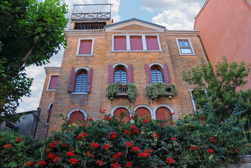 有花的美丽如画的房子在威尼斯的历史的中心 免版税图库摄影