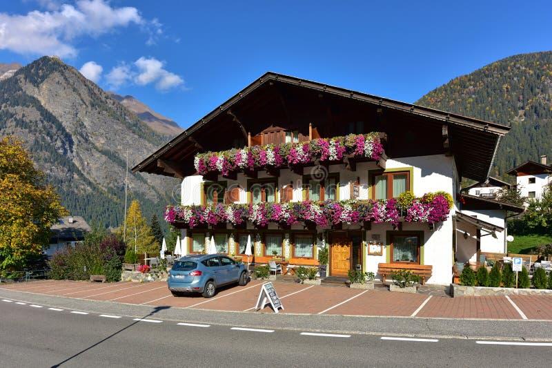 有花的美丽的乡间别墅在山背景  普拉特,波尔扎诺自治省,意大利村庄  库存图片