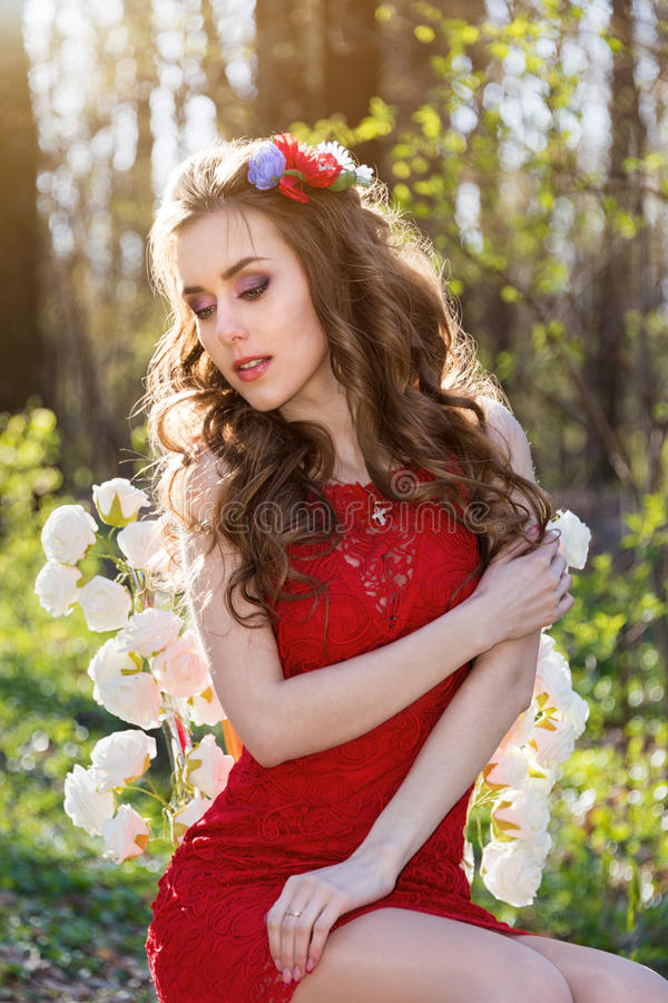 有花的美丽的少妇在她的头发在森林 图库摄影